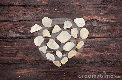 A heart shaped pebble stones on a old wood