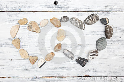 Two heart shaped pebble stones on a old wood