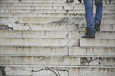 Man walking climb up in old stairs