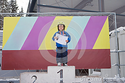 Portrait of young preschool boy, with medal for ending a ski sch