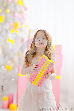 Little girl in an elegant dress presents a gift