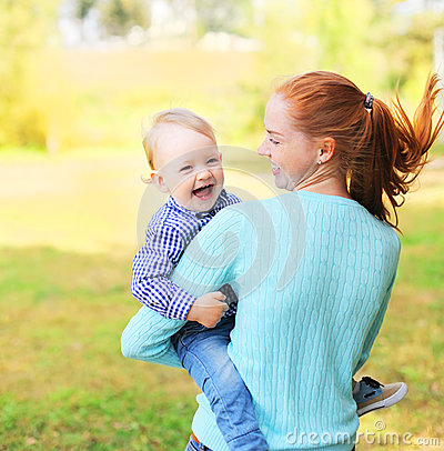 Happy cheerful smiling mother and son child having fun outdoors