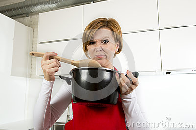 Home cook woman at kitchen holding cooking pot and spoon tasting soup in a funny disgusting bad taste face