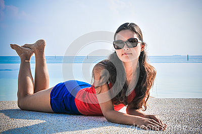 Portrait of young asian looking woman lie near swimming pool at tropical beach at Maldives