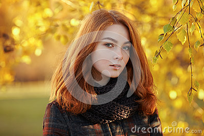 Close up portrait young beautiful redhead woman in scarf and plaid jacket against autumn foliage background cold season outdoors