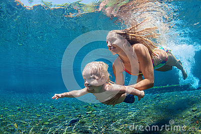 Mother with child swim and dive underwater in sea pool