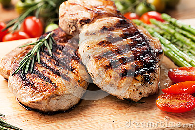 Grilled pork chop with rosemary leaf on wooden board