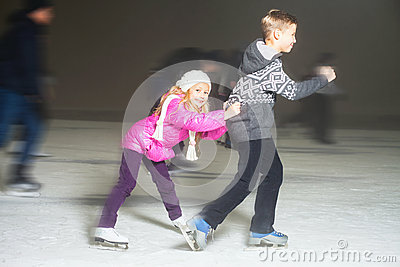 Happy children ice skating at ice rink, winter night