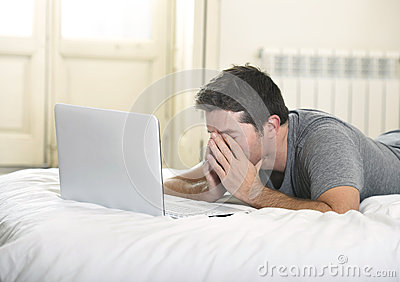 Young tired man lying on bed or couch working on computer laptop at home wireless connected to internet in technology concept