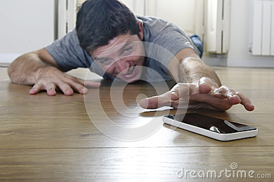 Man trying to reach mobile phone creeping on the ground in smart phone and internet addiction concept