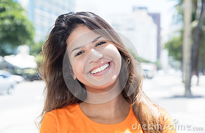 Laughing caucasian woman in a orange shirt in the city