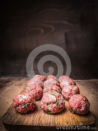 Raw minced meat balls with herbs and onions a vintage cutting board  close up