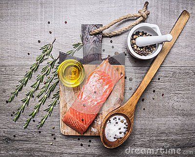 Salted salmon  fillet on a cutting board with delicious ingredients for cooking wooden rustic background top view