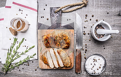 Appetizing chicken cooked in mustard sauce and cut into slices on a cutting board a knife, herbs, salt and pepper unmilled on