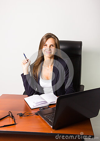 Pretty woman in a business suit sitting at a desk with computer.
