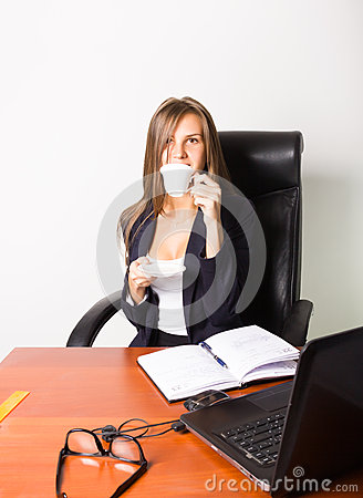 Pretty woman in a business suit sitting at a desk with computer. woman drinks coffee from a white cup