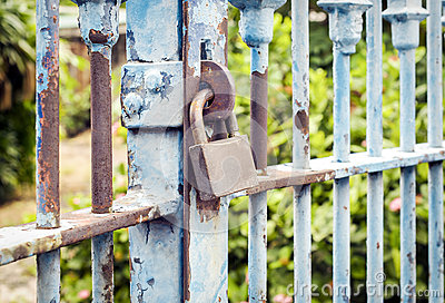 Old rusted lock on blue rusty iron gate