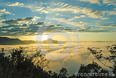 Beautiful rising sun in the early morning over sea of fog on hill of Phu Tok.