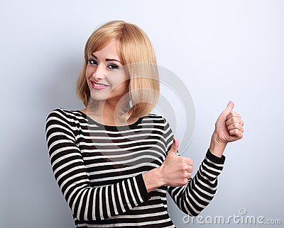 Blond happy smiling young woman showing thumb up sign by two han
