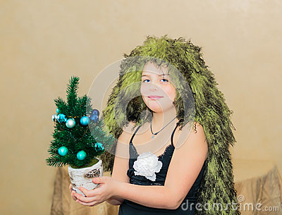 smiled beautiful little girl with unique hair cut holding small decorated miniature Christmas tree