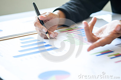 Asia business woman analyzing investment charts on desk.