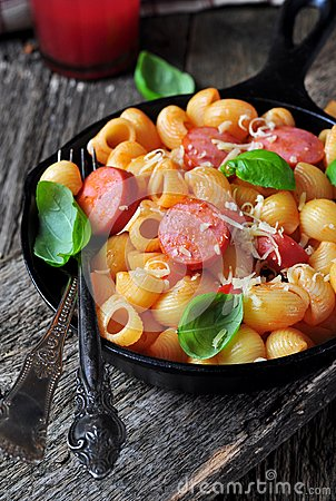 Pasta with sausages in tomato sauce with basil and cheese