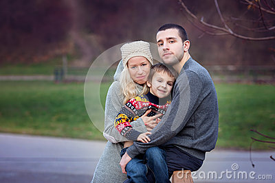 Young attractive family with kid, young adults having fun outdoo