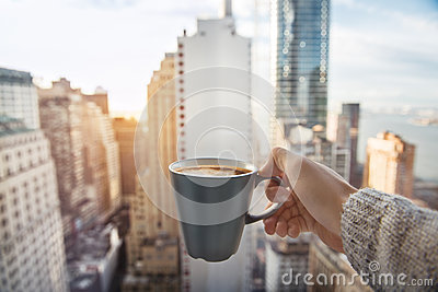 Man holding coffee cup in luxury penthouse apartments with view to New York City