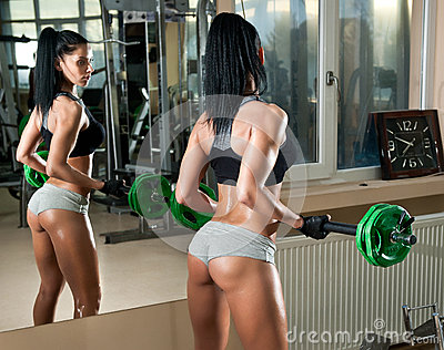 Gorgeous brunette working on her muscles in a gym, mirror reflection. Fitness woman doing workout. Sporty girl doing exercise