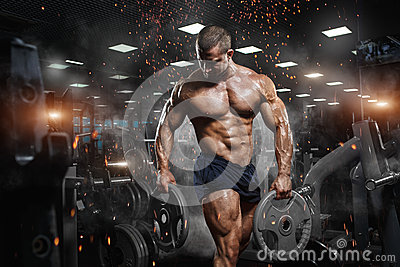 Muscular athletic bodybuilder fitness model posing after exercis