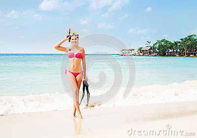Gorgeous, slim, cheerful girl posing with diving mask and flippers on the seacoast in Thailand