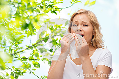 Unhappy woman with paper napkin sneezing