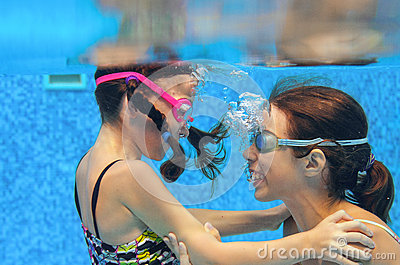 Children swim in pool underwater, happy active girls in goggles have fun under water, kids sport
