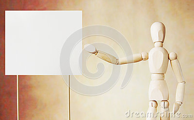 Wooden puppet points to blank white broadsheet with its hand