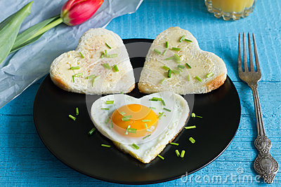 Valentine's Day abstract breakfast with egg heart and tulip