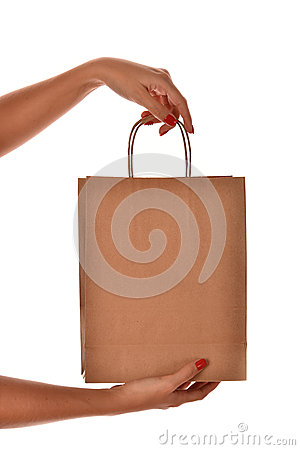 A female hand with red nail hold a paper shopping bag at the stu