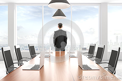 Businessman looking out the window in modern conference room wit
