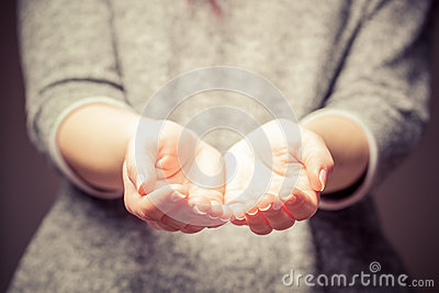 Light in young woman's hands. Sharing, giving, offering, taking care, protection.