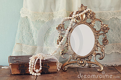 Antique blank victorian style frame and old book with vintage pearl necklace on wooden table. retro filtered image