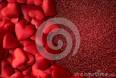 Little red satin hearts on red glitter texture, valentines or mothers day background