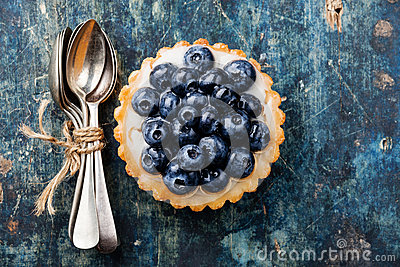 Blueberry tart and bunch of teaspoons
