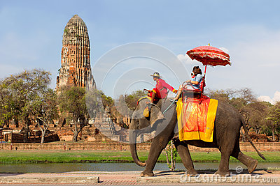 Tourists take an elephant ride around historic site at Wat Phra Ram, in Ayutthaya, Thailand