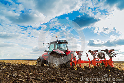 Farmer plowing stubble field with red tractor.