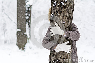 Woman hugging a tree in the winter forest .loving nature