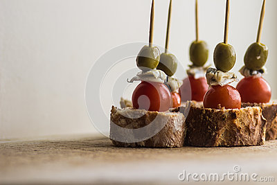 Pintxos Pintxo set, olive, anchovy, cherry tomato and bread on a Rustic Board, food from the Basque Country