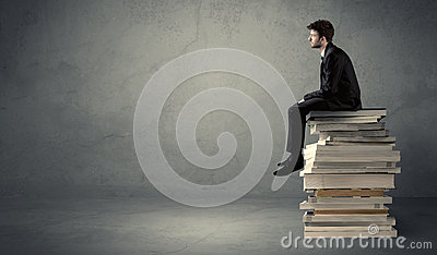 Stylish male seated on books