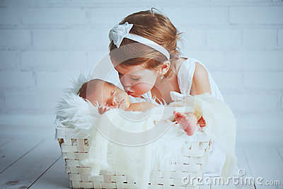 Children sister kisses brother newborn sleepy baby on a light