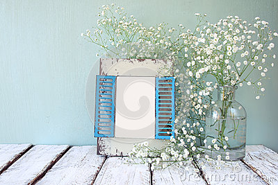 Old wooden frame next to white flowers on wooden table. template, ready to put photography