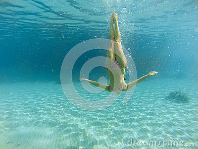 Good looking woman diving under the sea