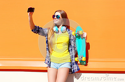 Pretty cool smiling girl in sunglasses with skateboard taking picture self portrait on smartphone